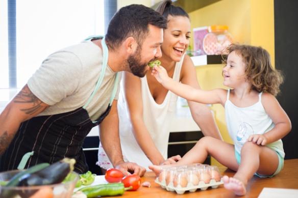 donna-che-guarda-la-figlia-che-alimenta-il-peperone-a-suo-padre_23-2147892125